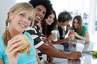Portrait of a young woman holding a burger with her friends sitting in the background