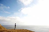 Man standing on cliff by ocean, Point Reyes National Park, California, USA