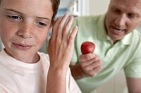 Close_up of a boy refusing an apple from his father