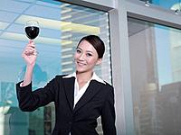 Businesswoman holding glass of wine