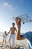 Close_up of a mans hand holding a model airplane with his children standing on the beach