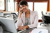 Business woman using laptop and cell phone in office