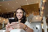 Portrait of smiling woman sitting in lobby with cell phone