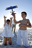 Close_up of a girl and her brother playing on the beach with their father standing behind them