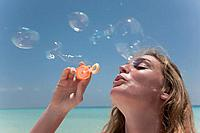 Woman blowing bubbles on beach