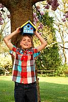 Boy holding birdhouse on his head