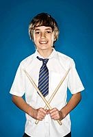 Portrait of schoolboy 10_12 holding drumsticks on blue background