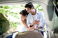 Couple hugging at open car trunk