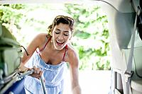 Smiling woman loading luggage into van