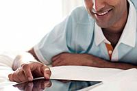 Close_up of smiling man using digital tablet