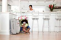 Boy 5_6 with beach toys sitting in suitcase in kitchen