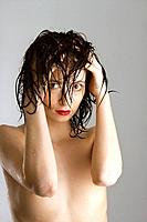 Portrait of bare attractive Caucasian redhead young woman with wet hair.