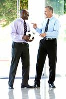 Two smiling men with soccer ball