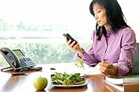 Woman using cell phone at desk, salad and apple on foreground