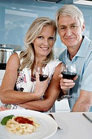 Portrait of a senior couple holding glasses of red wine and smiling at the kitchen counter