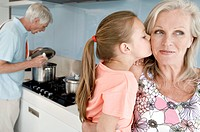Close_up of a girl kissing her grandmother with a senior man cooking in the background
