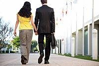 Back view of couple holding hands while walking down sidewalk