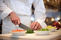 Mid section of chef chopping vegetables