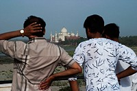 Rear view of three men with mausoleum in the background, Taj Mahal, Agra, Uttar Pradesh, India