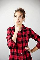 Studio portrait of young woman in checked shirt looking up