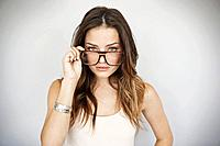 Young woman looking through glasses, studio shot