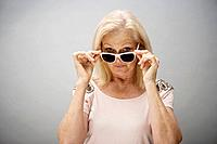 Portrait of senior woman looking through glasses, studio shot