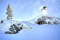 Snowboarder jumping from hillside
