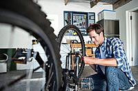 Smiling man repairing bike in garage