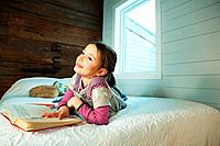 Young girl lying on bed reading book (thumbnail)