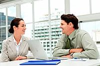 Businessman and businesswoman meeting in office with laptop