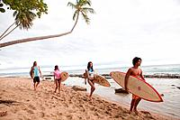 Four young friends carrying surfboards on beach (thumbnail)