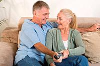 Mature couple both holding a remote control