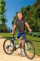 Senior male cyclist with bicycle
