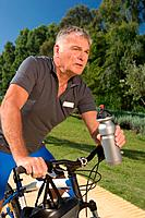Senior male cyclist holding water bottle