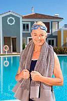 Mature woman by swimming pool with towel (thumbnail)