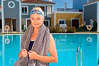 Mature woman by swimming pool with towel