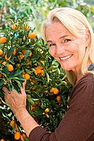 Mature woman by fruit tree