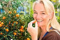 Woman tasting kumquat from tree