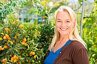 Mature woman by fruit tree (thumbnail)