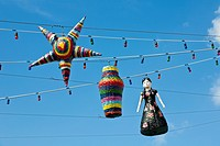 Pinatas hanging on strings of lights against blues sky in Cozumel, Mexico in the Caribbean Sea (thumbnail)