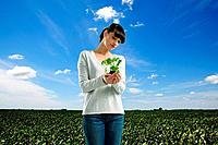 Young woman holding plant in field