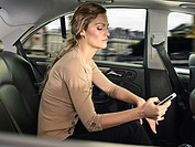 Woman using cell phone in car