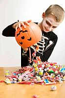 Caucasian boy in skeleton dumping out Halloween candy
