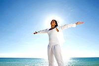 Mixed race woman standing near ocean with arms outstretched