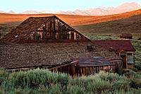Old wooden house at dawn, with Sierra Nevada snow_tipped mountain range in distance, blue sky, sage brush foreground, Bodie pioneer village, Californi...