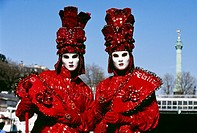 Two men dressed up in costume stand next to Bastille Square during a Venetian festival in Paris