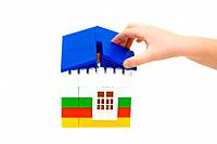 hand puts the roof on the house constructed from toy blocks