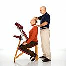 Caucasian middle_aged male massage therapist massaging neck of Caucasian middle_aged woman sitting in massage chair.