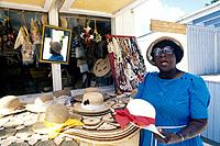 Local woman Sarah Hutchieson in front of her stall selling straw work/ basketware. Holding hat. Family Islands.