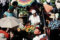 Local women stallholders surrounded by fruit and vegetables at colourful busy market.
